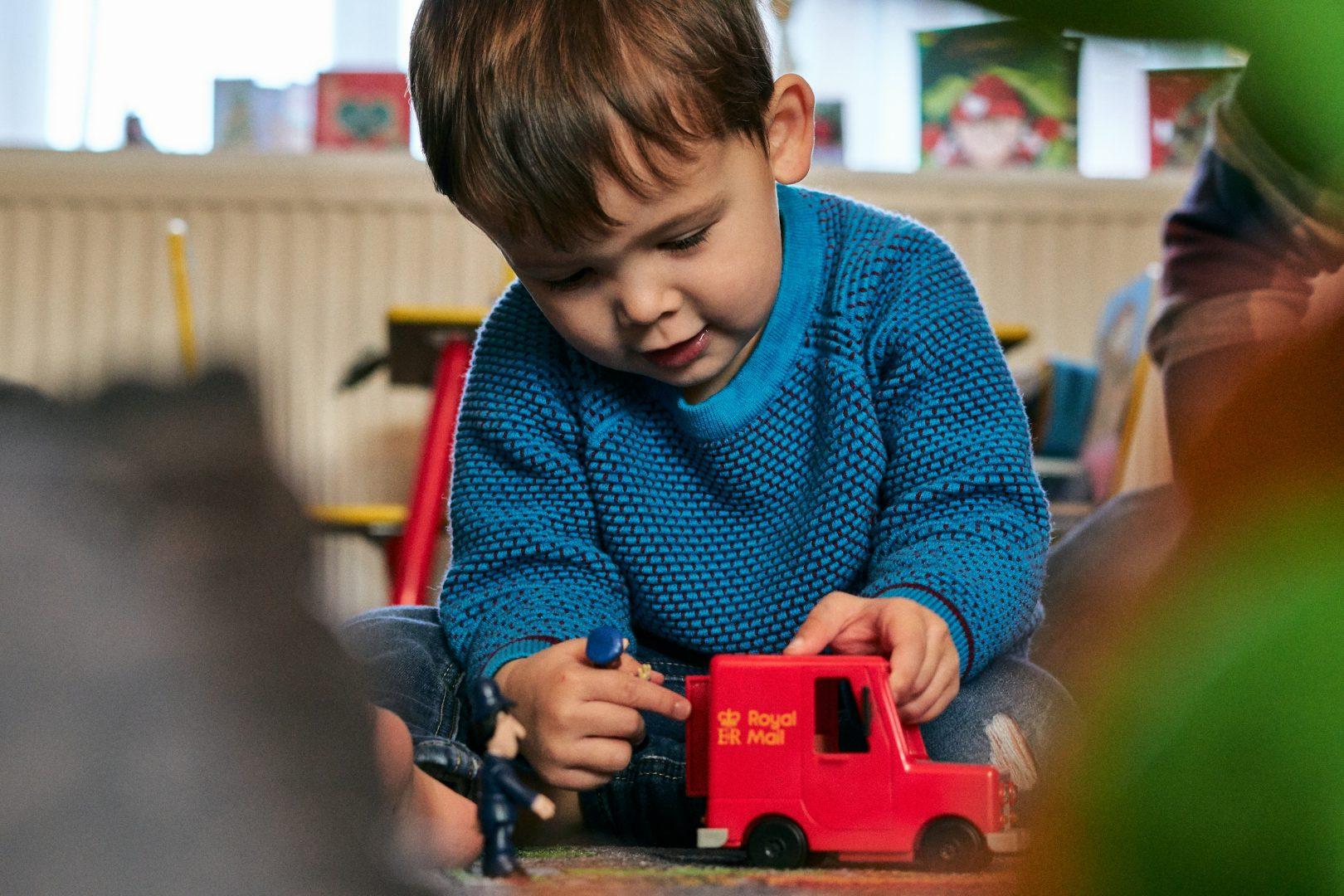3 year old boy plays with postman pat red van