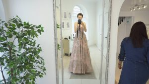 wedding vlogger stands in mirror in a blush pink dress