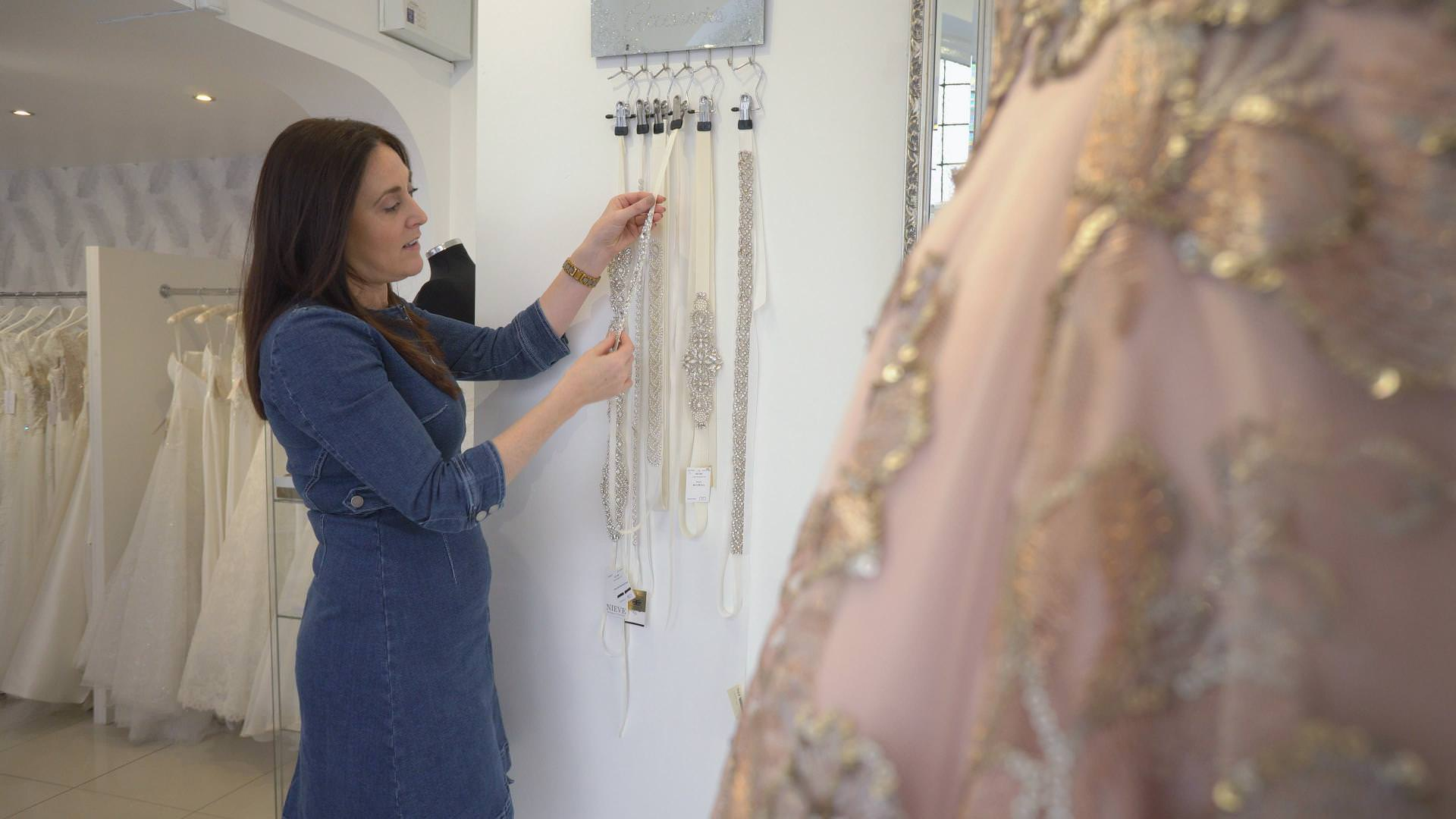 a bridal boutique owner looks at belts