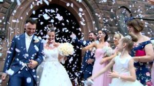 a bride and groom showered in pink confetti in the wirral