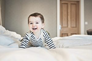 little boy on parents bed smiling during family photography shoot