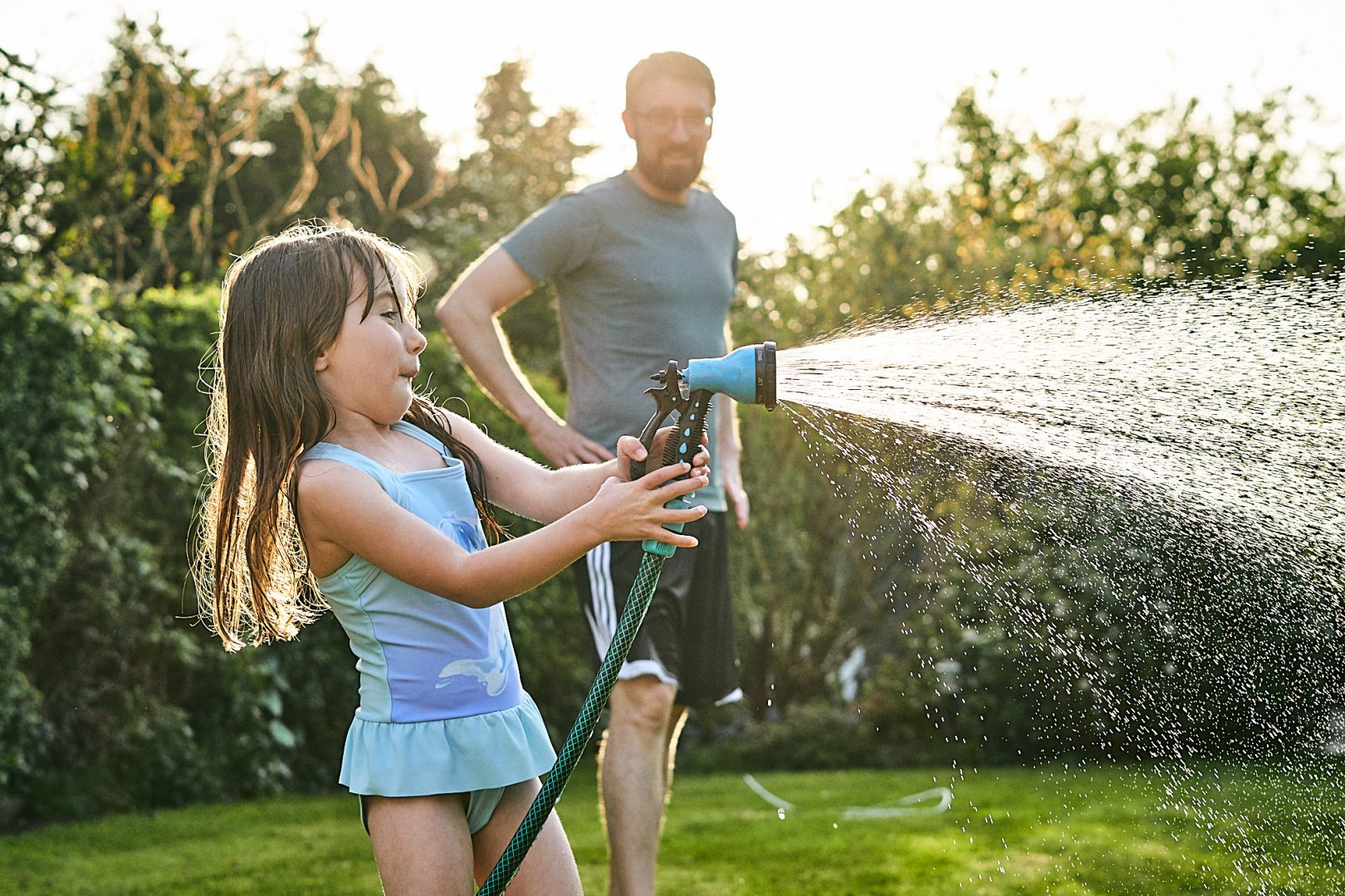 funny photo of girl spraying hose in garden in lancashire