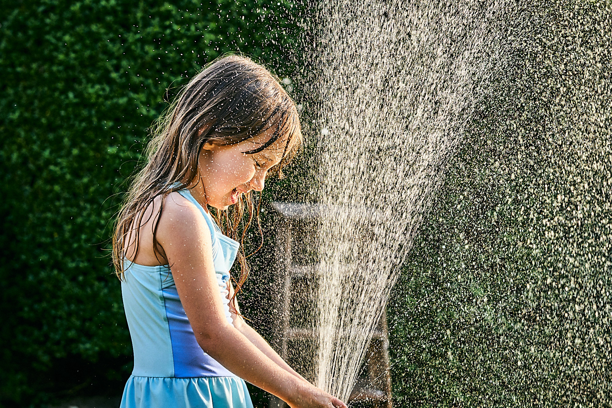 girl plays with hose in garden for photos