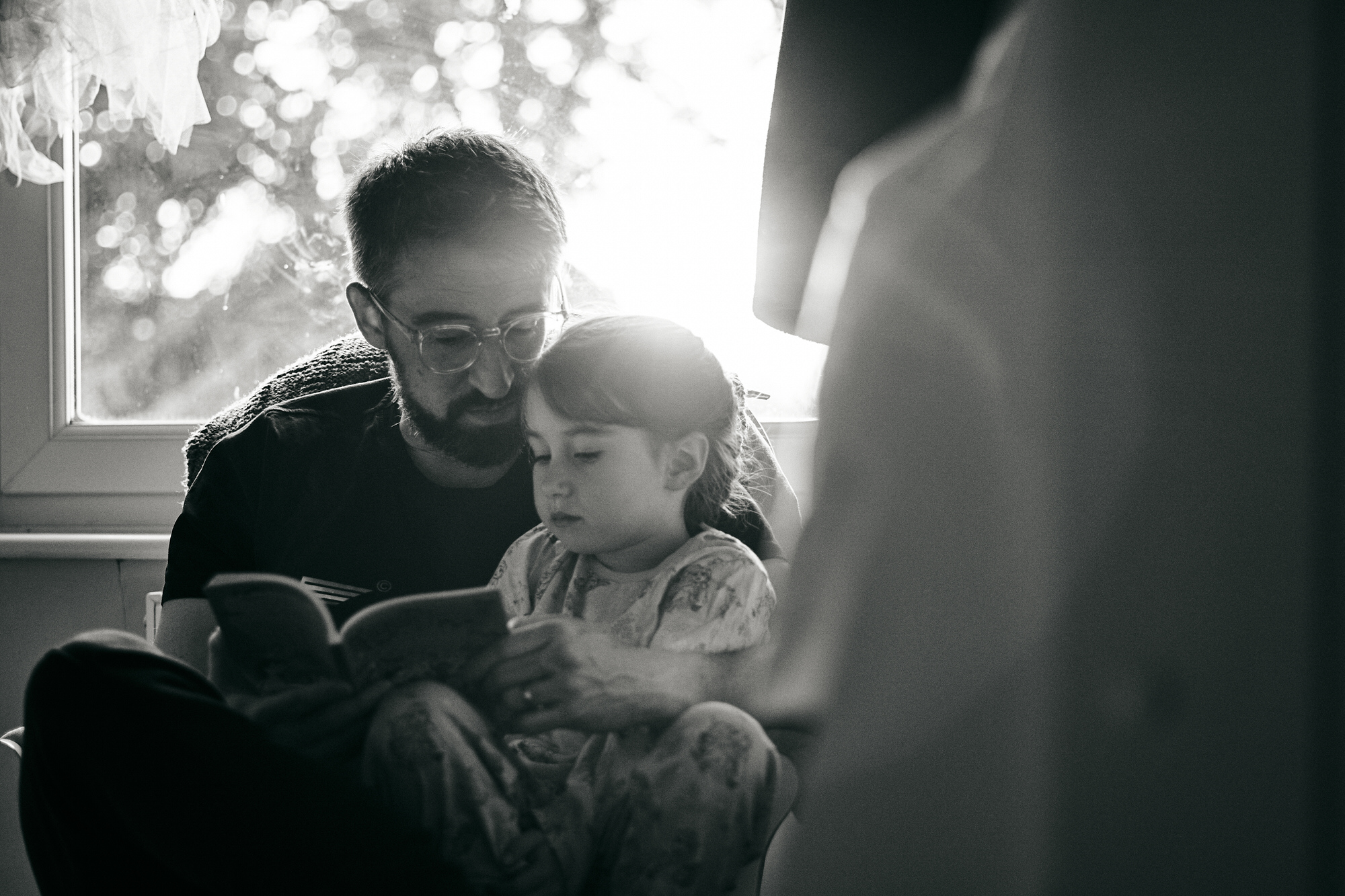 dad and daughter cuddle and read together