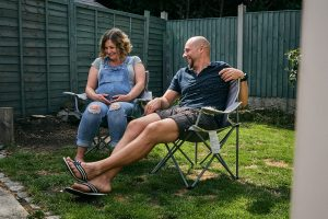 parents to be laugh in garden during photoshoot