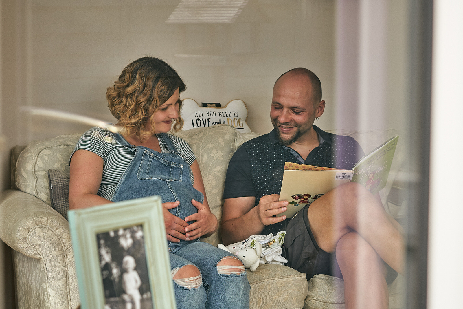 couple smile at baby bump sat at home