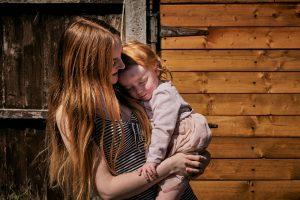 mum cuddles toddler during lockdown photo shoot