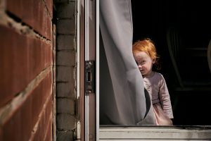little red haired girl hides behind curtain for photo
