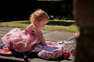 little girl plays with her dolls