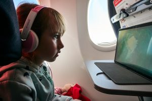 young girl watches tablet during flight to Turkey