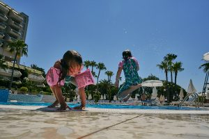 children jumping in swimming pool on holiday