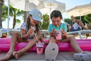 children drink by the pool on holiday