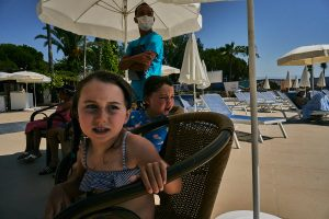 children sit by pool with staff in PPE on holiday