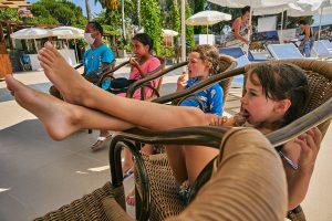 girl sits and licks icecream on holiday