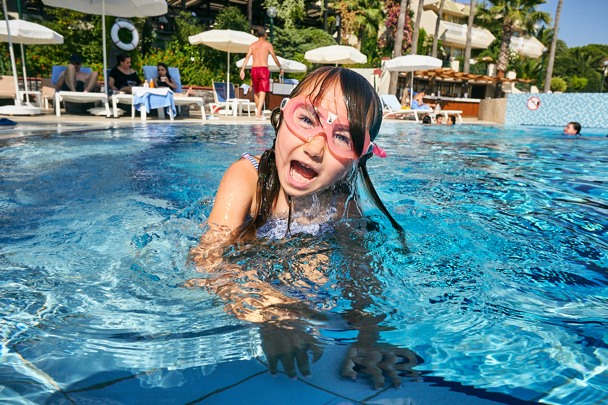 fun picture of girl pulling face in holiday pool
