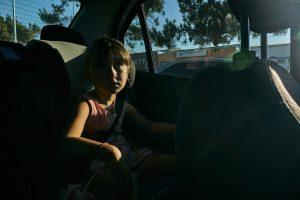 girl sat in hire car in the sun light