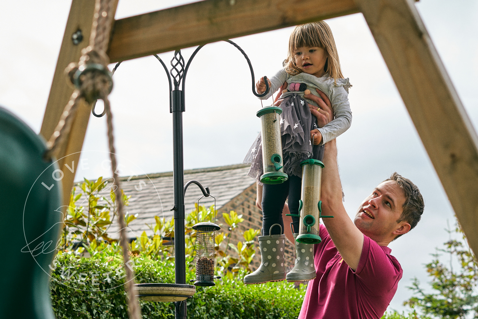 photo dad lifts girl to feed birds in garden