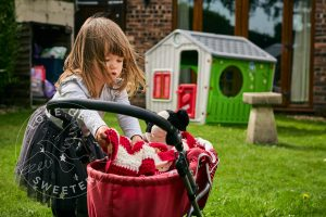 photo of girl with jessie cat and pram during family photoshoot