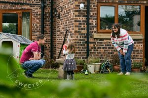 documentary photo of family playing in garden