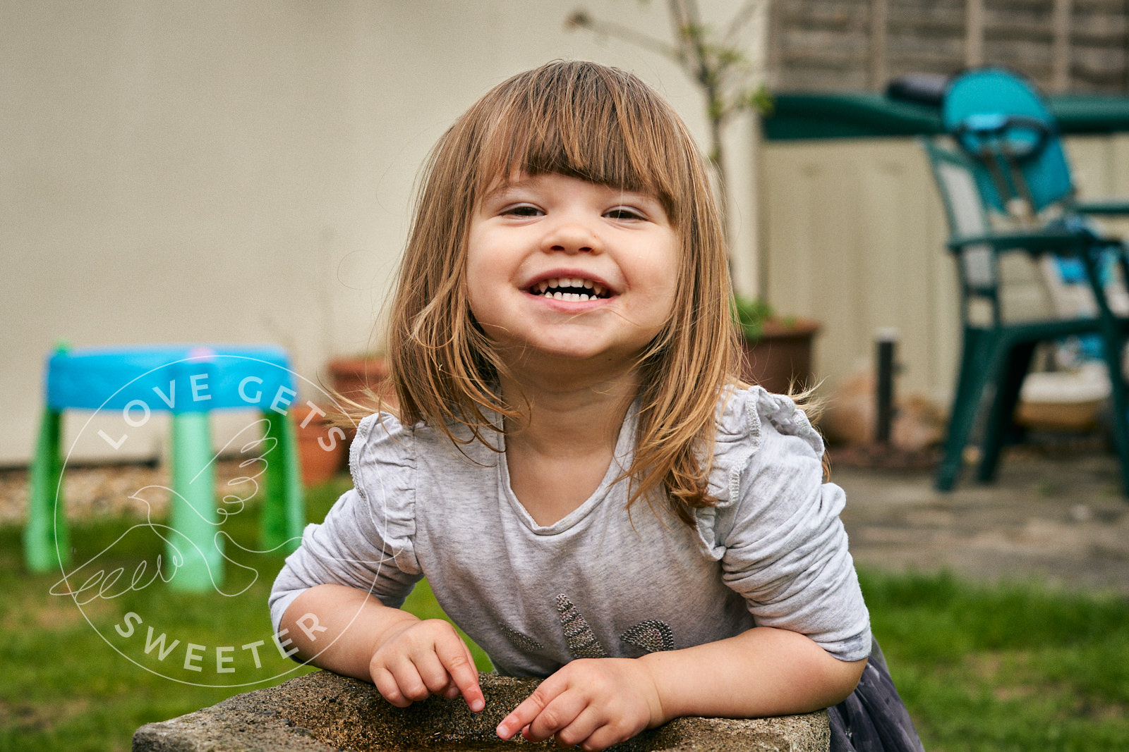 little girl grins at camera in fun family photo