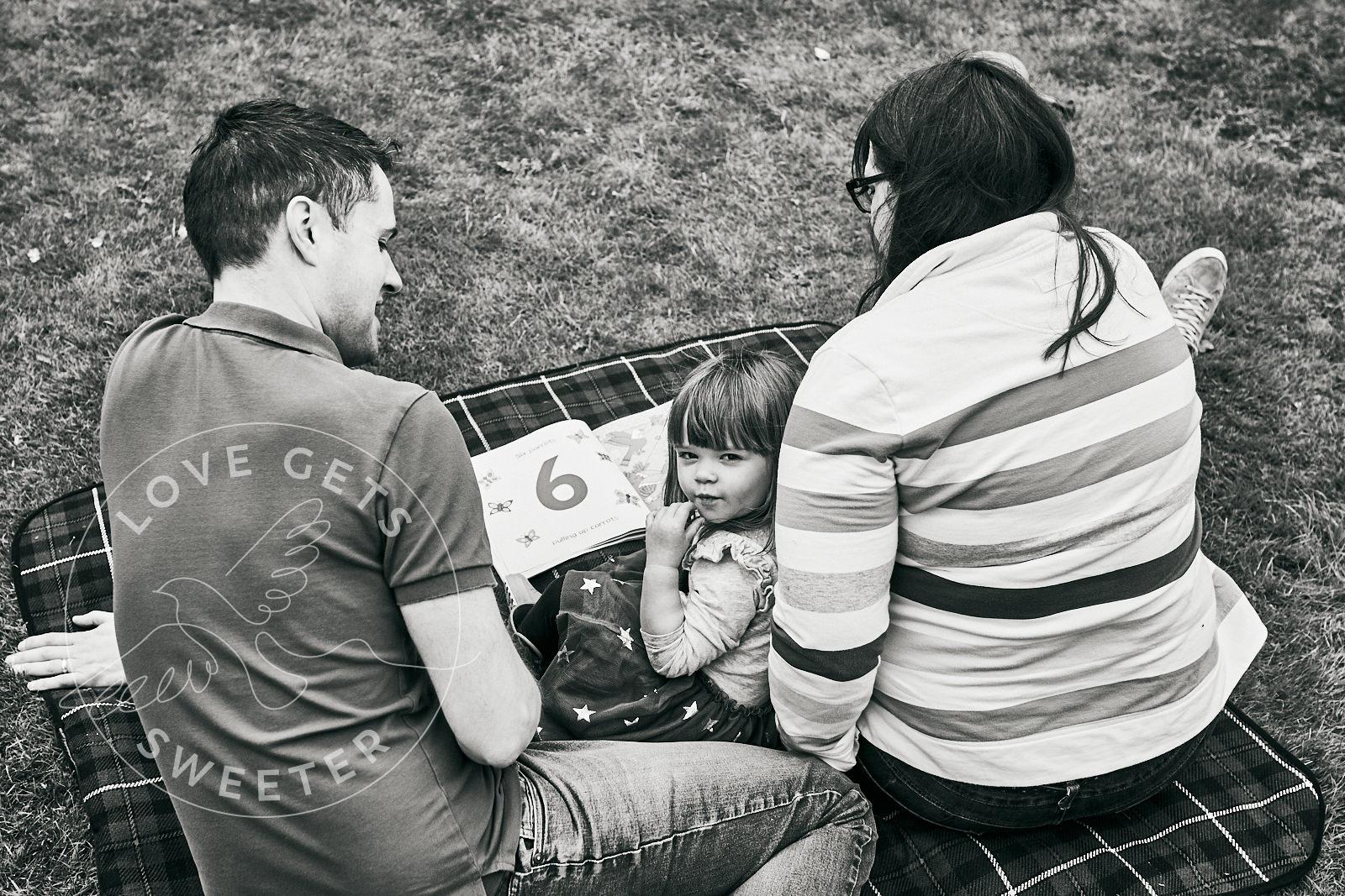 family reading on blanket during natural family shoot