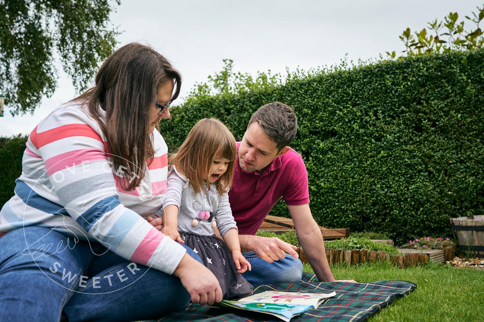family relax on blanket in garden reading