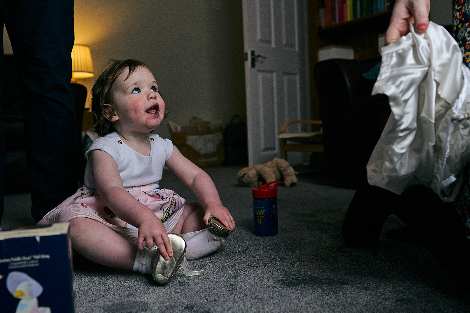 little girl tries on sisters glitter naming day shoes