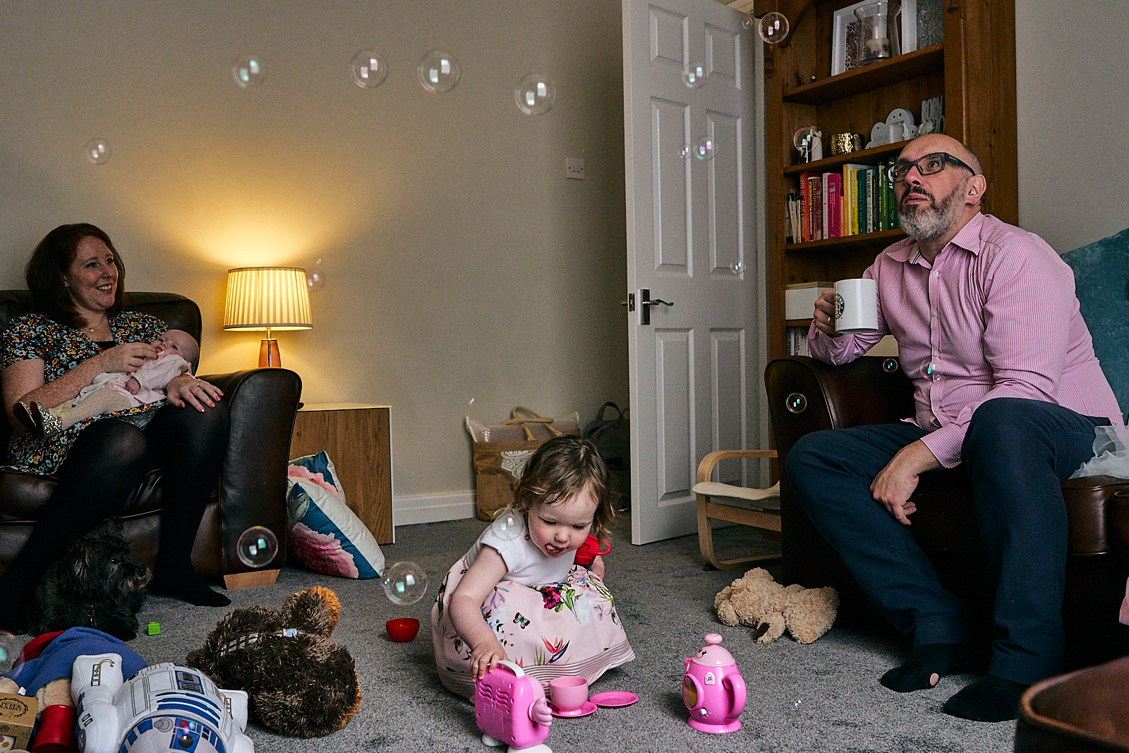 family sit in living room after naming ceremony in ramsbottom