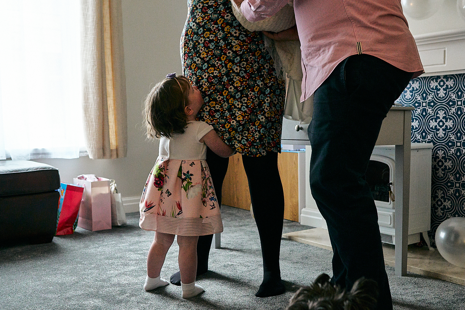 child holds mums leg during naming ceremony at home