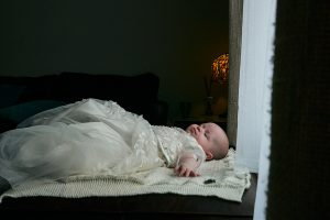 baby girl lays asleep in christening dress
