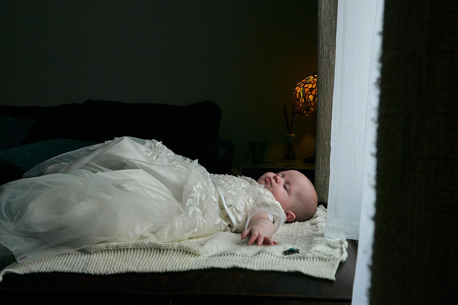 baby girl lays asleep in christening dress