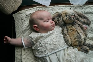 photo of baby asleep in naming gown