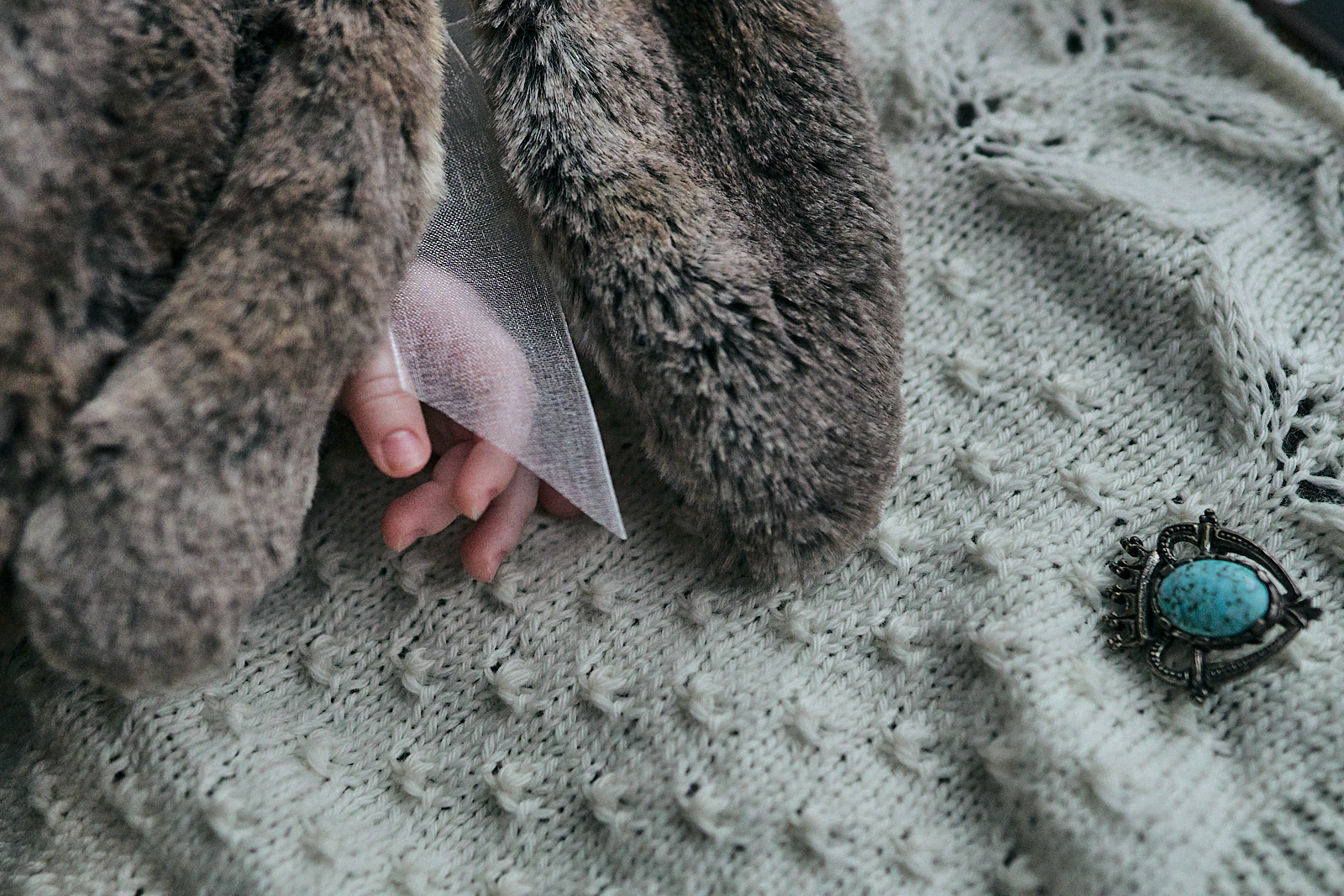 close up photo of baby girls hand on christening blanket