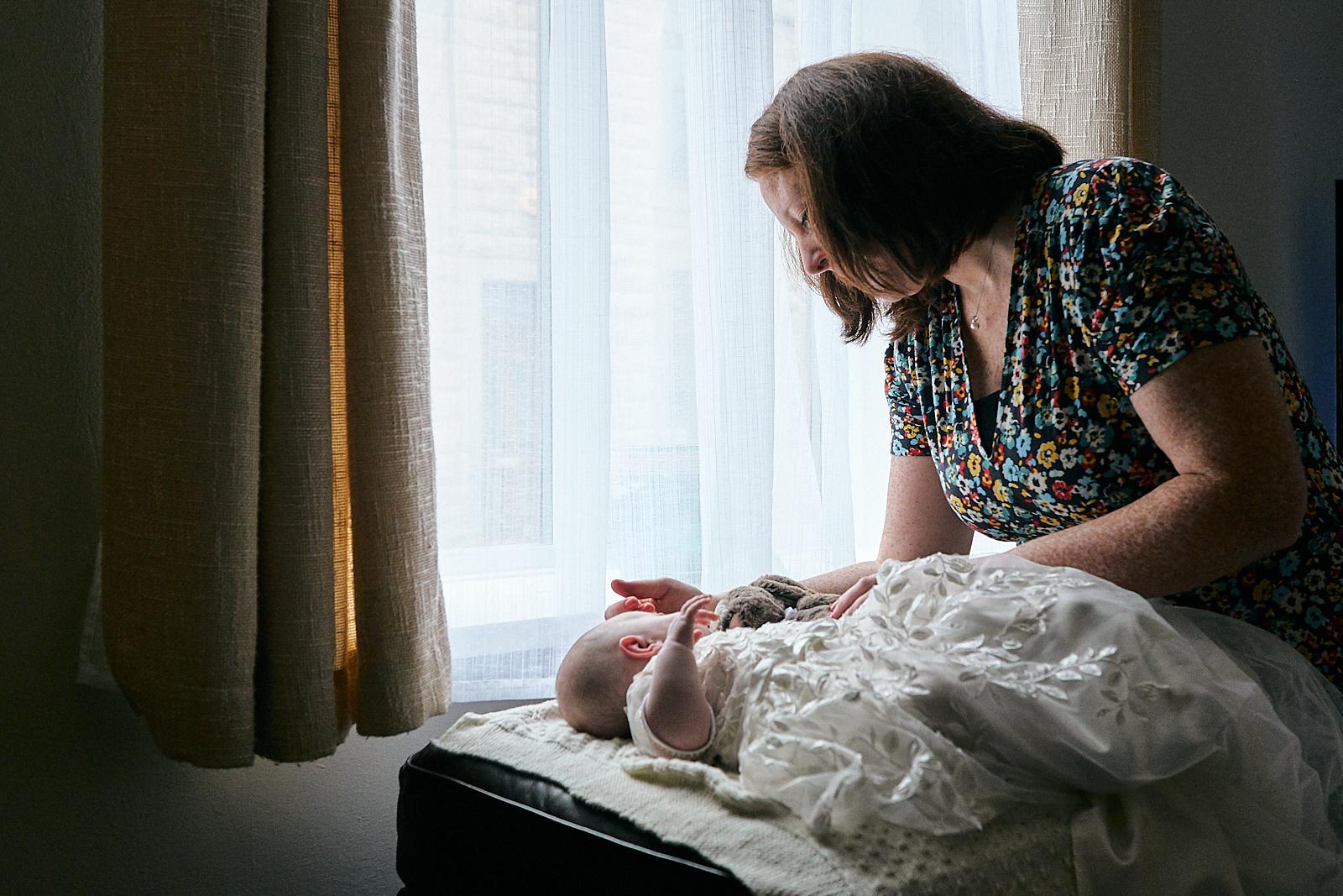natural photo of mum stroking baby girls head asleep