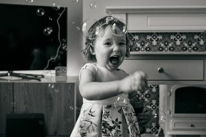 photo of little girl squeals at bubbles during naming day
