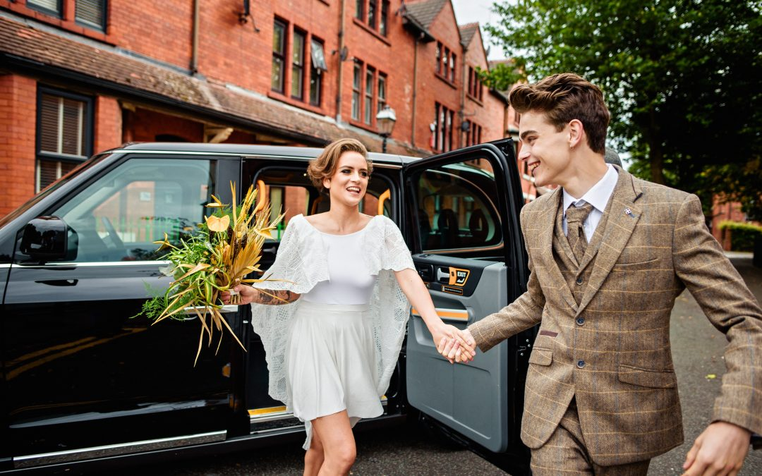 bride and groom jump out of Manchester Taxi for Salford Lads Wedding