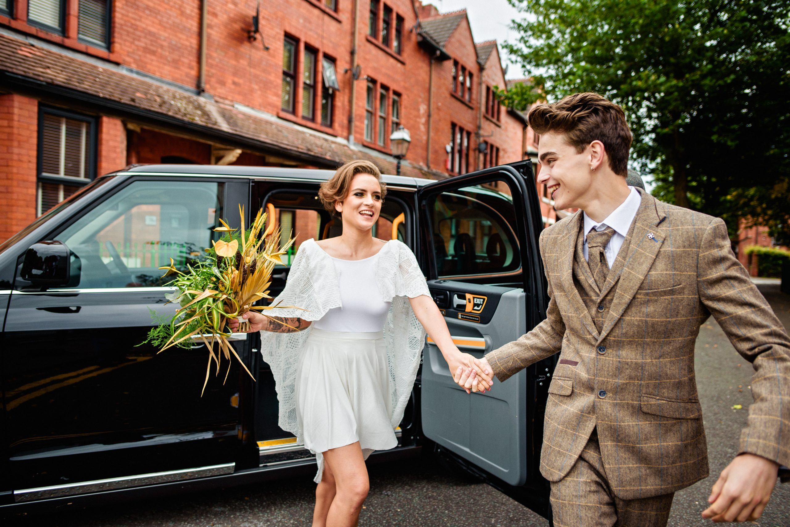 bride and groom jump out of Manchester Taxi for Salford Wedding