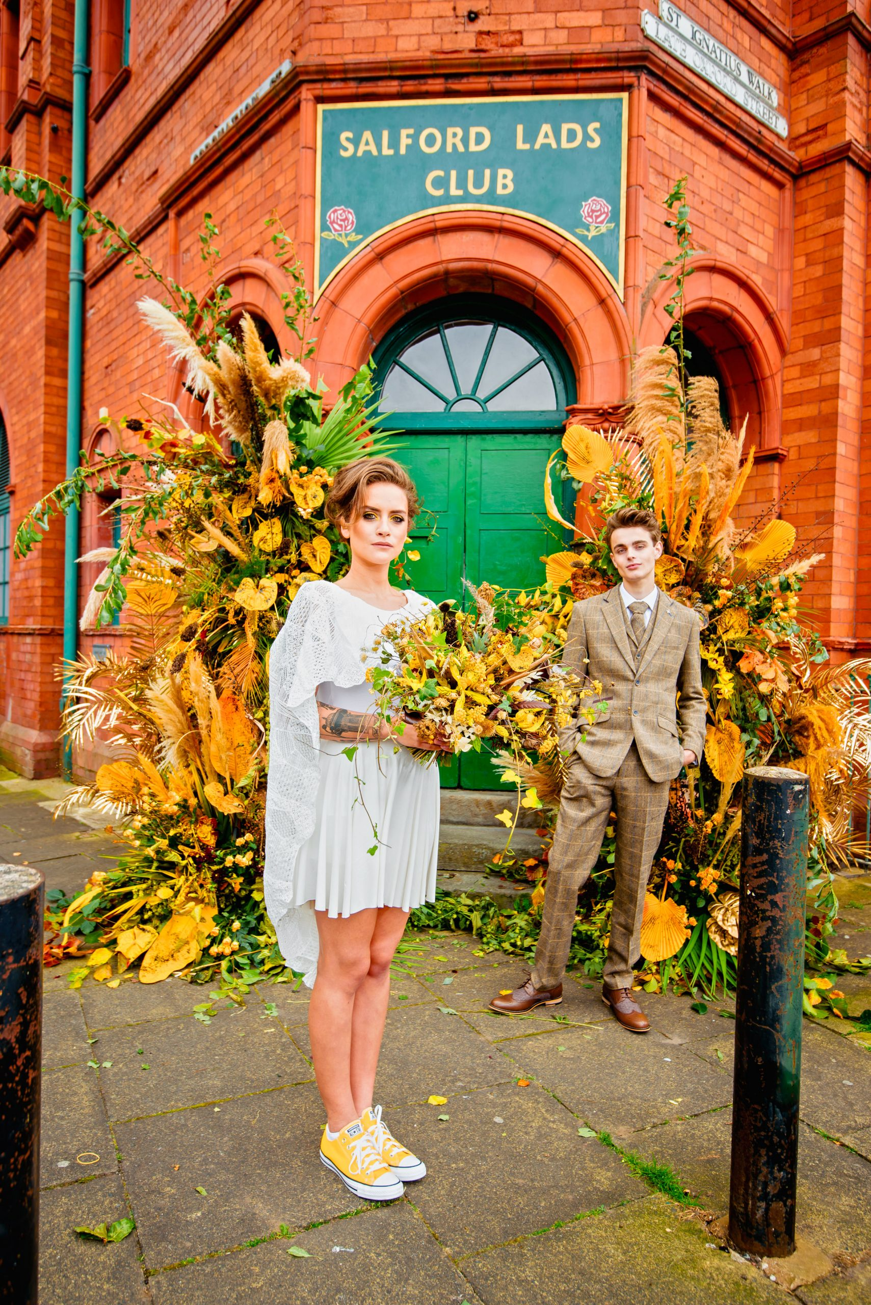 cool bride and groom posing outside Salford Lads Club wedding