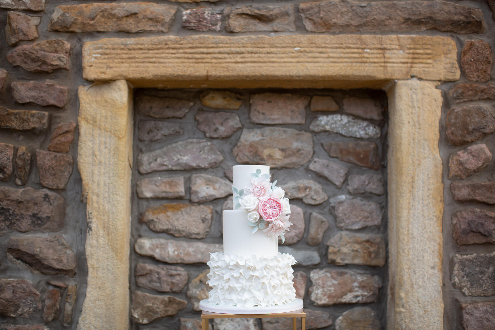 simple white wedding cake beside stone barn wall