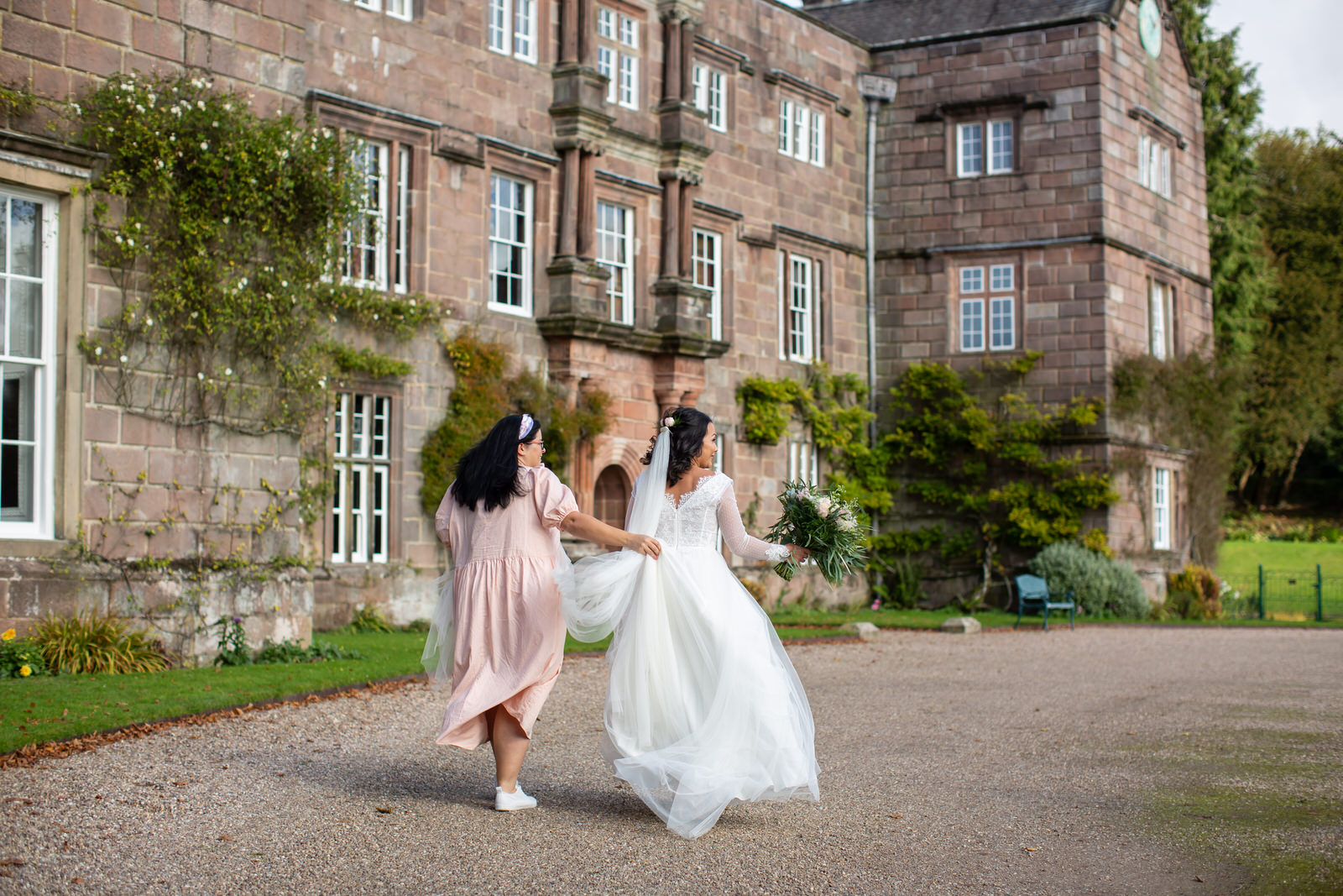 lottie brides helps bride with dress during shoot
