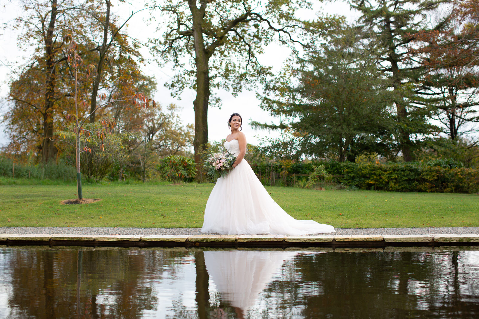 bride walks beside ceremony lily pond at Browsholme