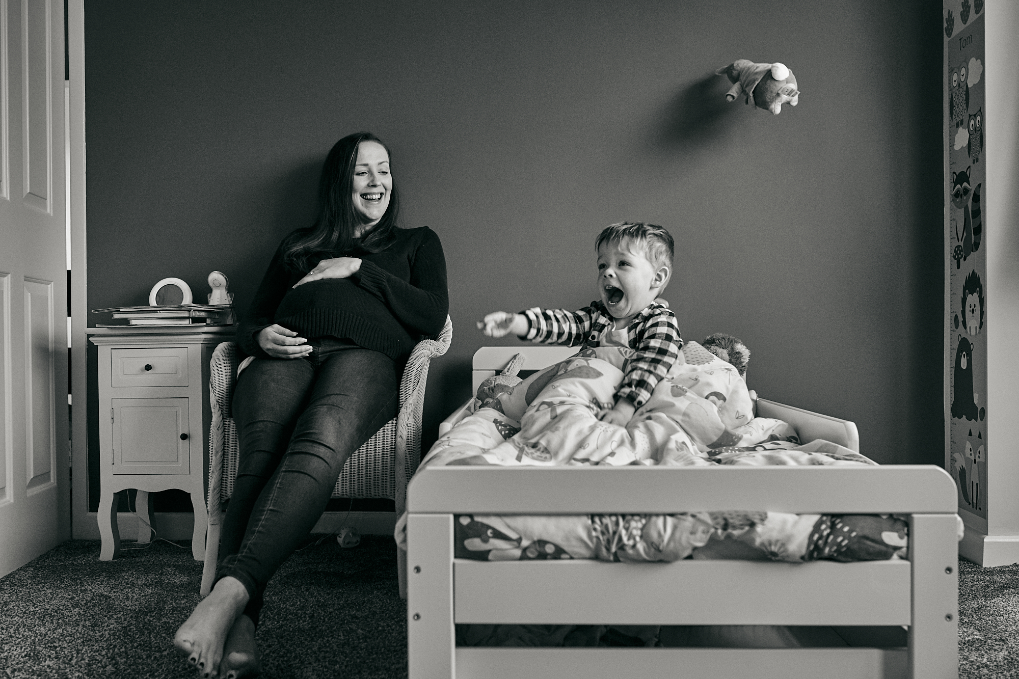 fun documentary photo of mum and son laughing and throwing toys
