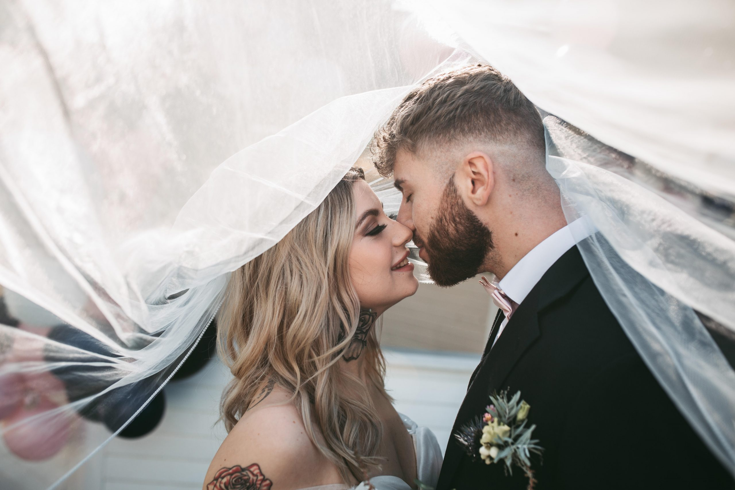 photo of bride and groom kiss under veil