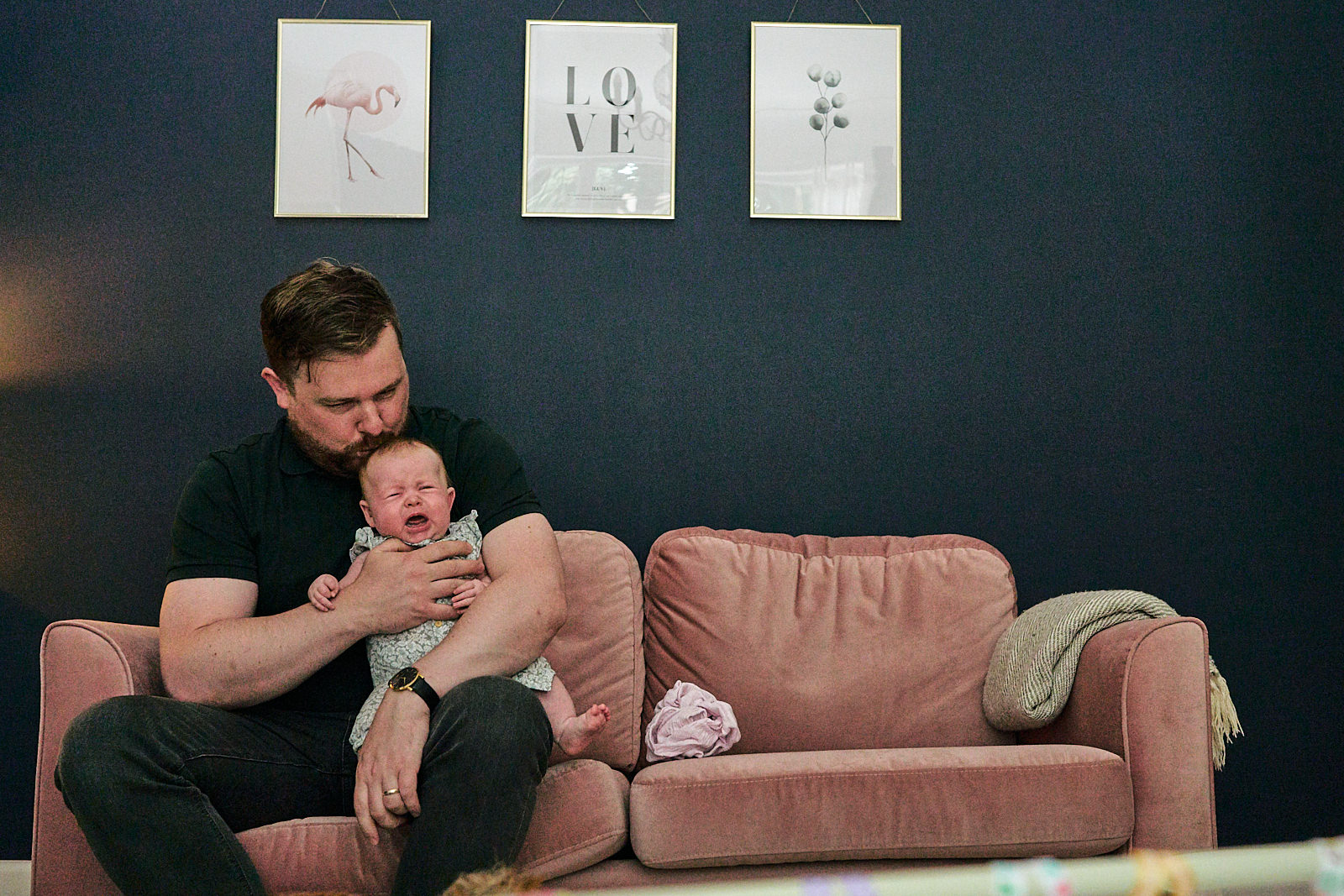 dad kisses baby sat on sofa for photographer