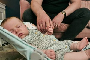 sleeping baby holding dads finger for natural photo
