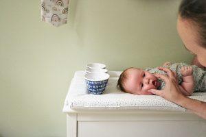 mum squishes babys cheeks for natural photo