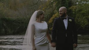 newlywed couple smile at each other for videographer