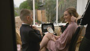 bride smiles at son in his wedding tux