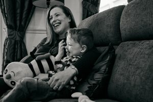 mum and son laugh on sofa during natural photoshoot