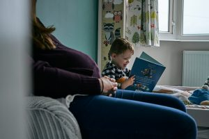 natural family photograph of boy reading to bump